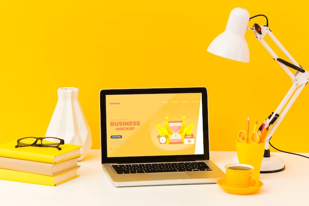 Vista frontale della scrivania con lampada e laptop