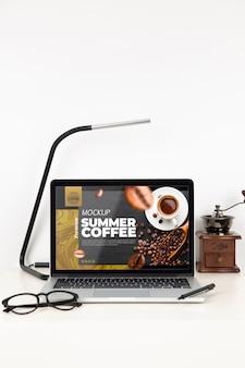Vista frontale della superficie della scrivania con laptop e occhiali