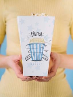 Vista frontale della tazza del popcorn della tenuta della donna