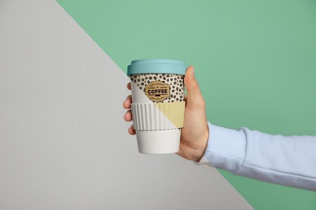 Vista frontale della tazza di caffè tenuta in mano
