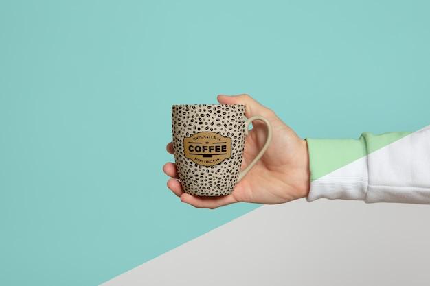 Vista frontale della tazza tenuta a mano