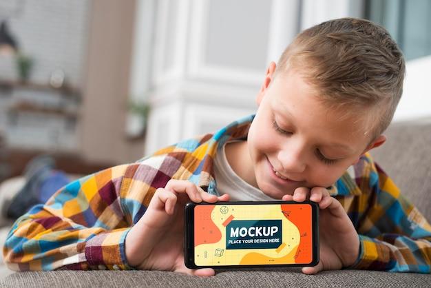 Vista frontale di smiley kid sul divano tenendo lo smartphone