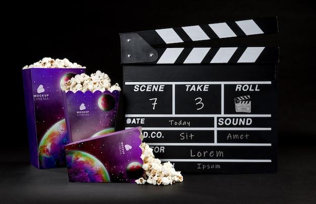 Vista frontale di tazze di popcorn cinema con ciak