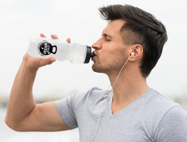 Vista lateral del agua potable del hombre después de hacer ejercicio