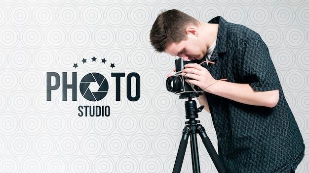 Vista lateral del fotógrafo trabajando con cámara