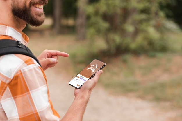 Vista lateral del hombre sonriente con smartphone mientras acampa