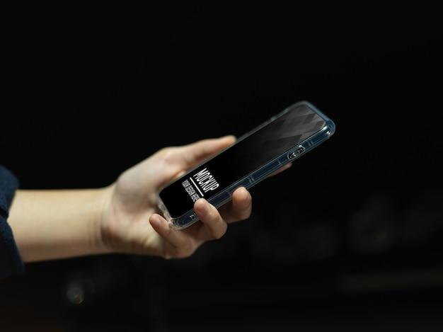 Vista lateral de la mano femenina que sostiene la maqueta del teléfono inteligente