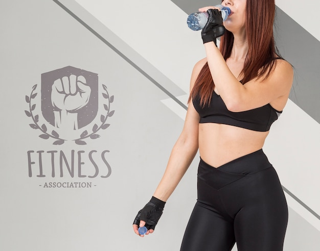 Vista lateral de la mujer fitness agua potable para botella