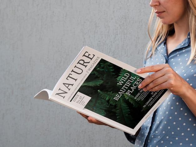 Vista lateral mujer sosteniendo una revista de naturaleza