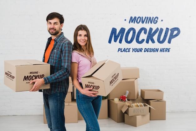Vista lateral de la pareja posando con cajas de mudanza