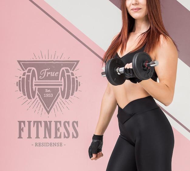 Vista laterale della donna atletica che tiene i pesi