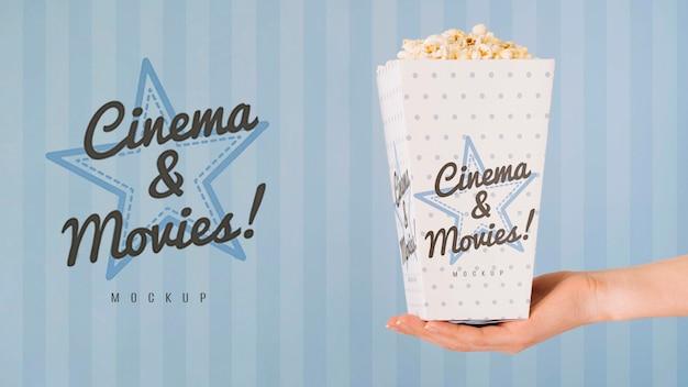 Vista laterale della mano che tiene tazza di popcorn