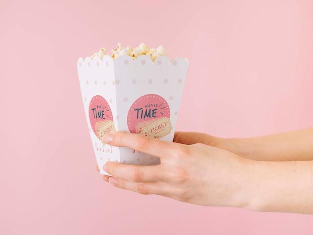 Vista laterale delle mani che tengono la tazza del popcorn