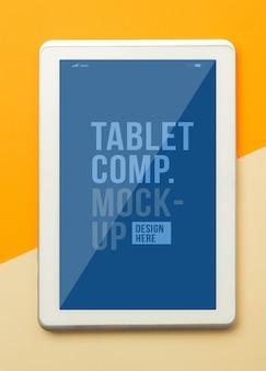 Vista piana laico e superiore della scrivania arancione tavolo da ufficio con modello di modello di tablet computer per il vostro disegno.