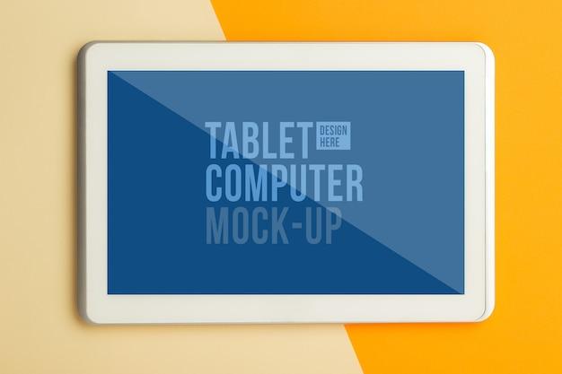 Vista piana laico e superiore della scrivania tavolo ufficio arancione con modello di mockup di tablet computer per il vostro disegno. spazio di lavoro moderno