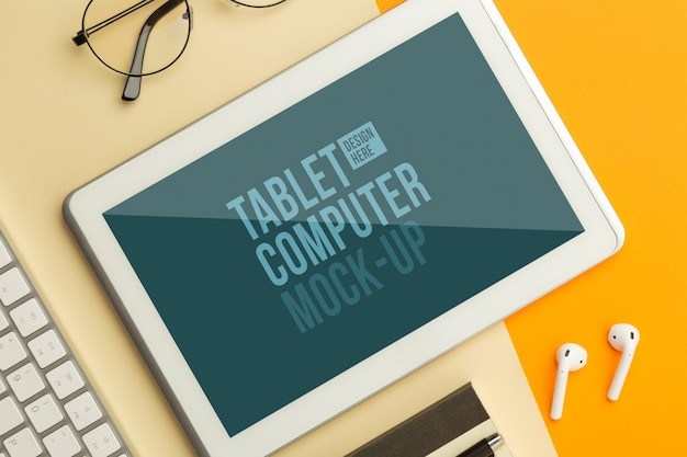 Vista plana endecha, superior del escritorio de mesa de oficina naranja con plantilla de maqueta de tableta y auriculares inalámbricos, teclado, cuaderno, gafas, bolígrafo. espacio de trabajo moderno