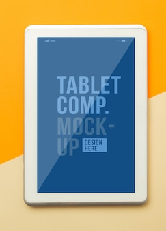 Vista plana endecha, superior del escritorio de mesa de oficina naranja con plantilla de maqueta de tableta para su diseño.