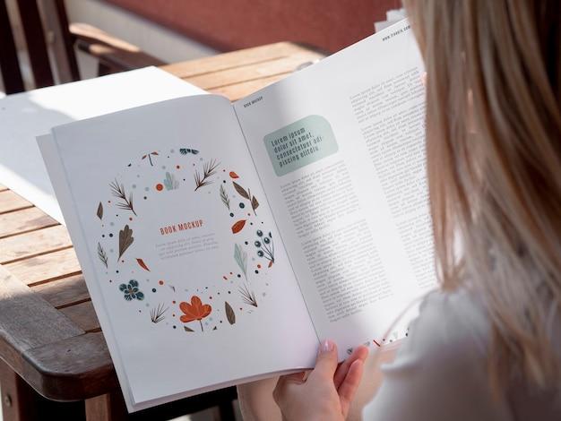 Vista posterior mujer mirando en un libro de naturaleza simulacro