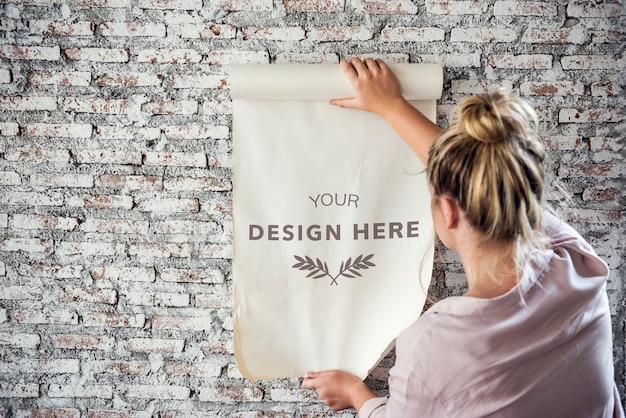 Vista posterior de la mujer que sostiene el papel del espacio de diseño