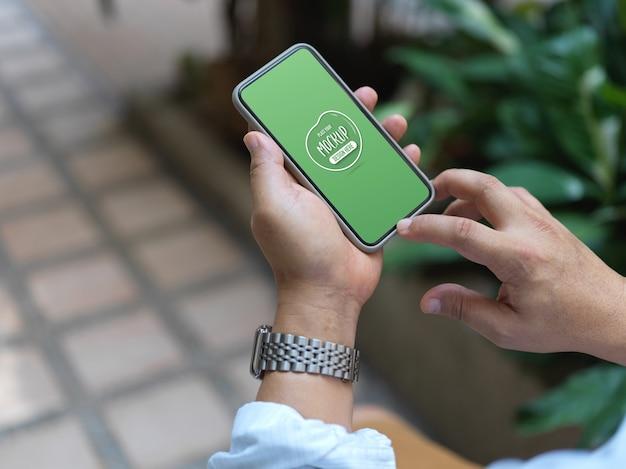 Vista ravvicinata sulle mani che tengono smartphone con mockup dello schermo