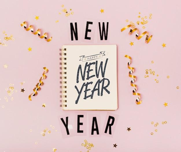 Vista superior año nuevo letras minimalistas en el bloc de notas