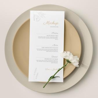 Vista superior del arreglo de la mesa con flor de primavera y maqueta de menú en platos