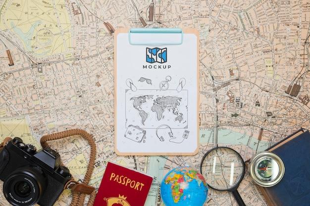 Vista superior del bloc de notas con elementos básicos de viaje y cámara