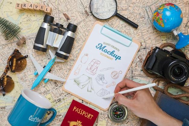 Vista superior del bloc de notas de maqueta con elementos esenciales de viaje y cámara
