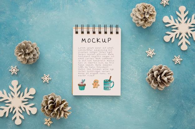 Vista superior del bloc de notas con piñas y copos de nieve