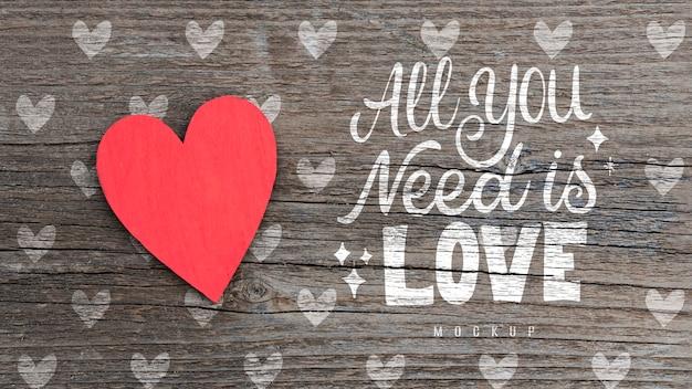 Vista superior del corazón de papel sobre fondo de madera con mensaje de amor