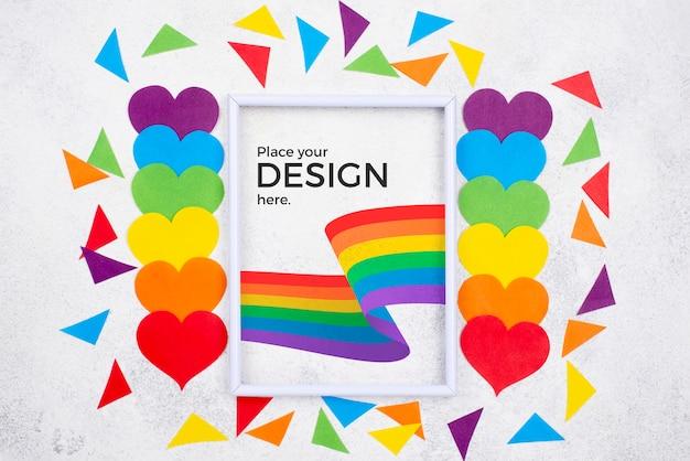 Vista superior de corazones de colores del arco iris con formas de bandera y papel