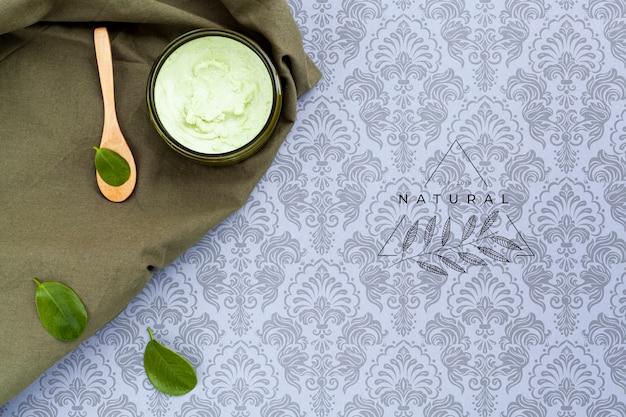 Vista superior de crema natural de mantequilla corporal sobre maqueta de fondo liso