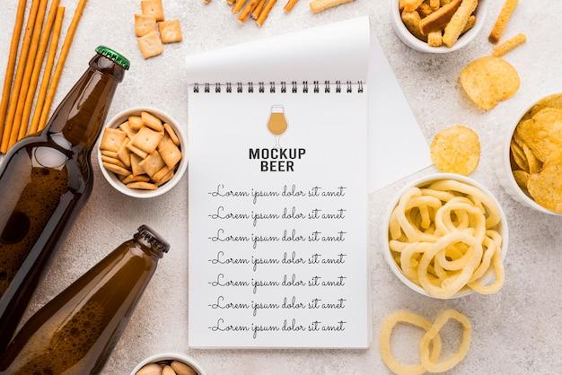 Vista superior del cuaderno con botellas de cerveza y variedad de bocadillos