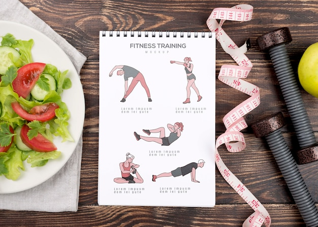 Vista superior del cuaderno de ejercicios con cinta métrica y pesas