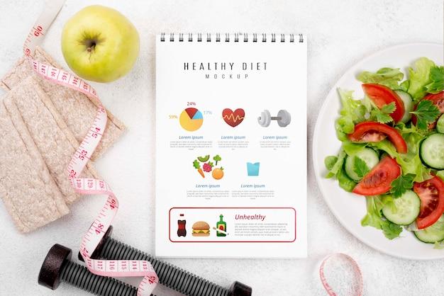Vista superior del cuaderno de ejercicios con ensalada y pesas