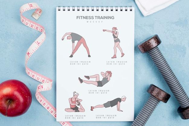 Vista superior del cuaderno de ejercicios con manzana y pesas