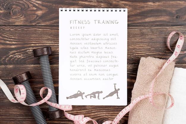 Vista superior del cuaderno de ejercicios con pesas y cinta métrica