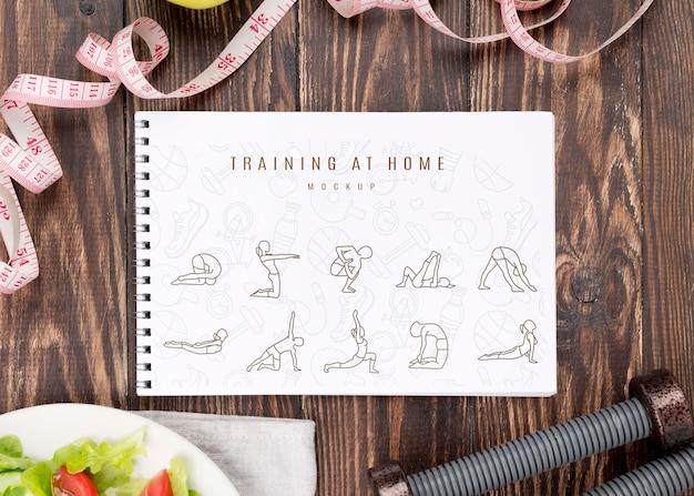 Vista superior del cuaderno de ejercicios con pesas y ensalada