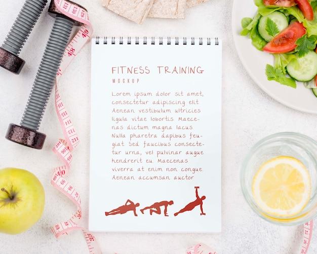 Vista superior del cuaderno de ejercicios con pesas y manzana