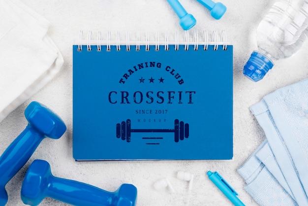 Vista superior del cuaderno de ejercicios con saltar la cuerda y pesas