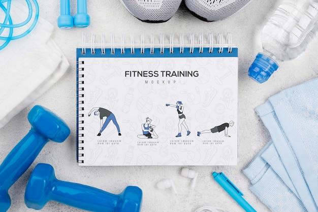 Vista superior del cuaderno de ejercicios con zapatillas y pesas