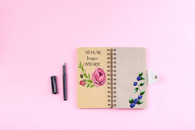Vista superior del cuaderno de espiral kraft y la página abierta en blanco sobre fondo rosa