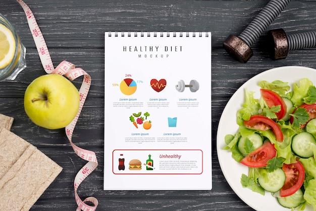 Vista superior del cuaderno de fitness con plato de ensalada
