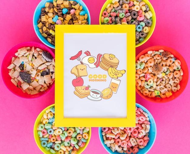 Vista superior de cuencos de cereales y marco con fondo rosa