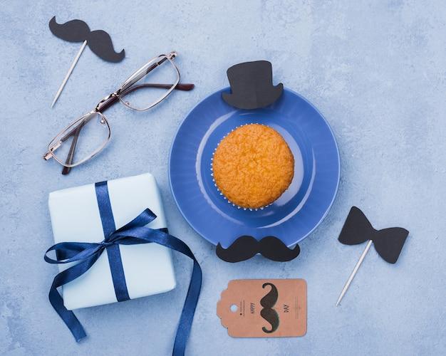 Vista superior de cupcake con gafas y regalo para el día del padre