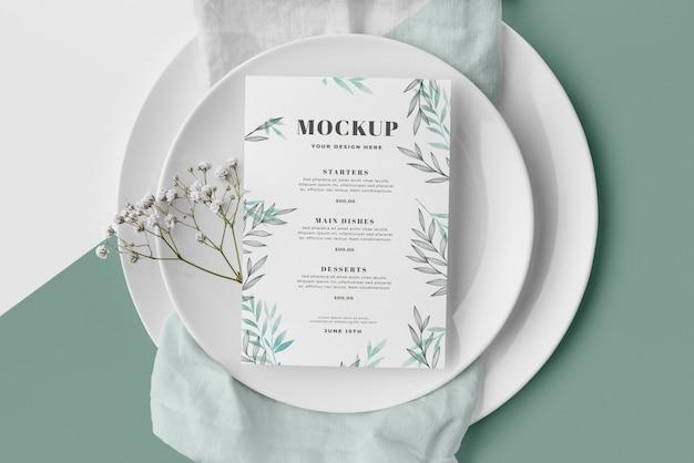 Vista superior de la disposición de la mesa con maqueta de menú de primavera y platos