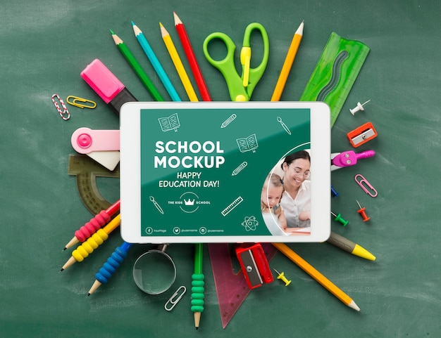 Vista superior de los elementos esenciales de la escuela y la tableta para el día de la educación