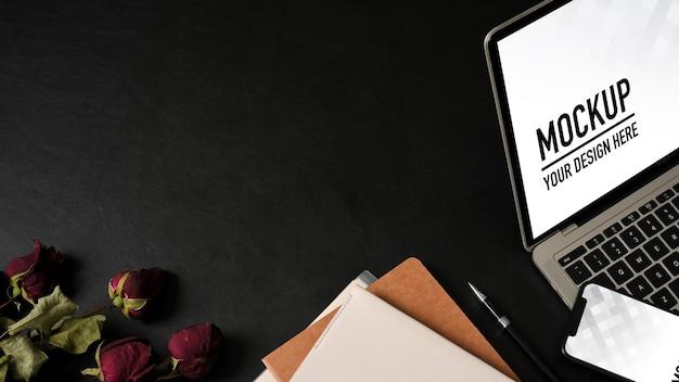 Vista superior del espacio de trabajo con computadora portátil, maqueta de teléfono inteligente