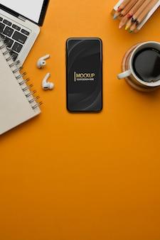 Vista superior del espacio de trabajo con papelería de taza de café de teléfono inteligente portátil
