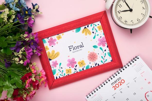 Vista superior de la flor de primavera con calendario y marco